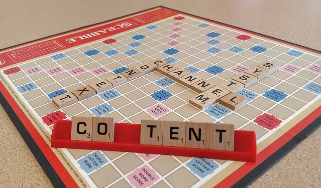 "a scrabble board with ""context"", ""channel"", and ""systems"" played, and ""co*tent"" in the foreground, ready to be placed on the board."